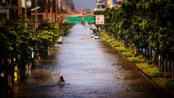 Hombre cruzando calle inundada a bordo