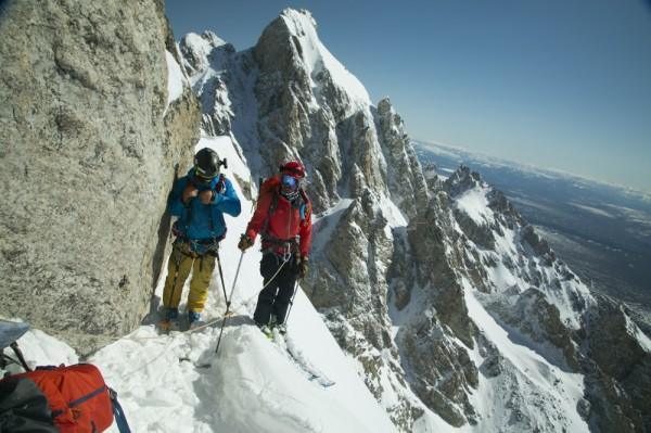Skiers walk along a steep slope