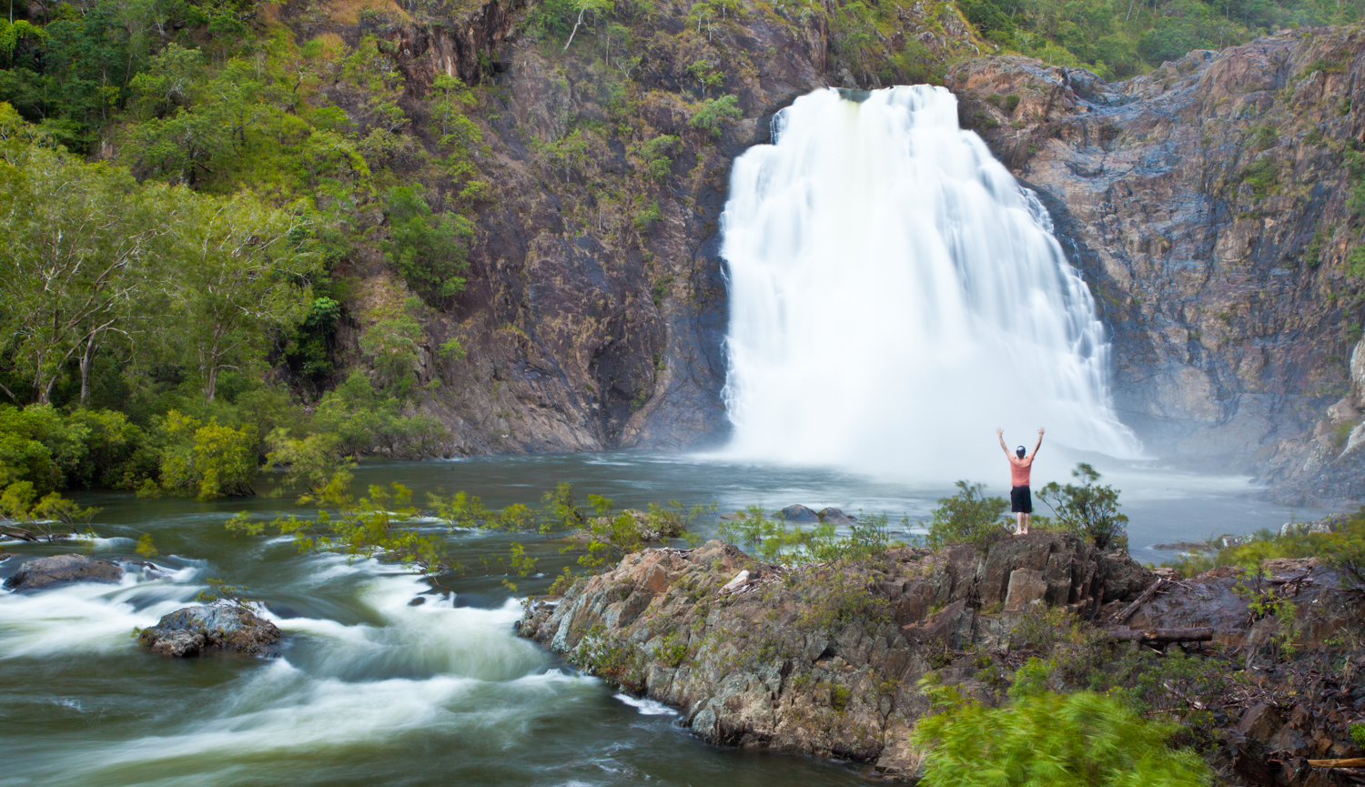 A figure stands in front of waterfall with arms raised