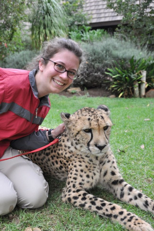 A woman poses beside a cheetah