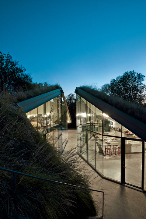 A concrete and glass house built into the ground