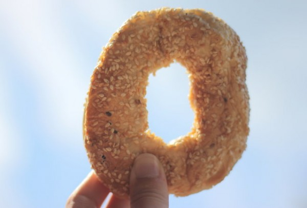 A bagel being held up to the sky