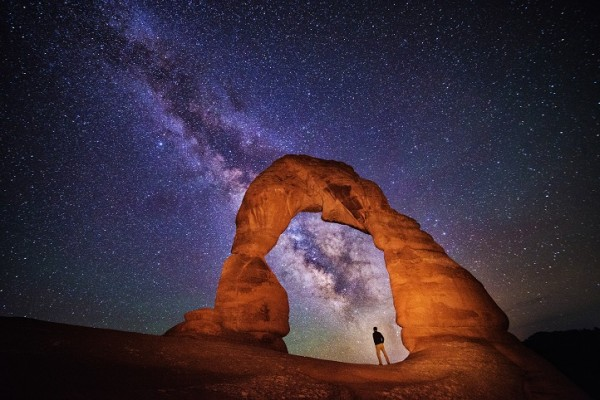A small figure stands under a rock arch at Arches. The Milky Way spans the scene