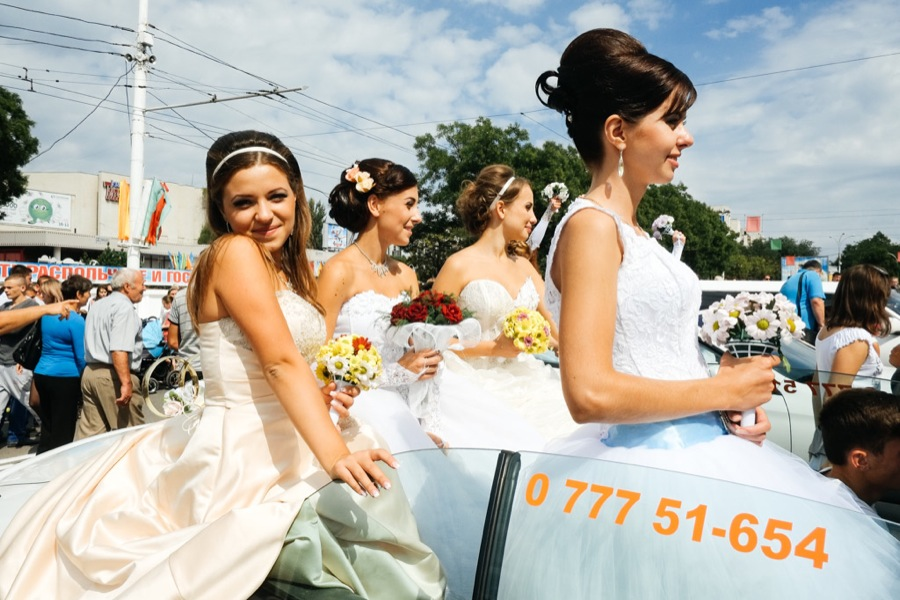 People wearing wedding dresses in a parade