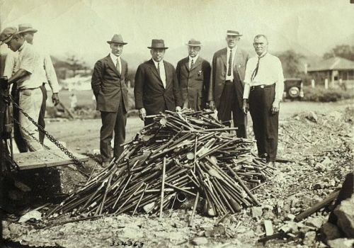People standing by a pile of opium pipes