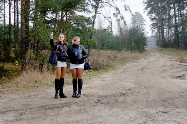 Two women wearing matching mini skirts and boots
