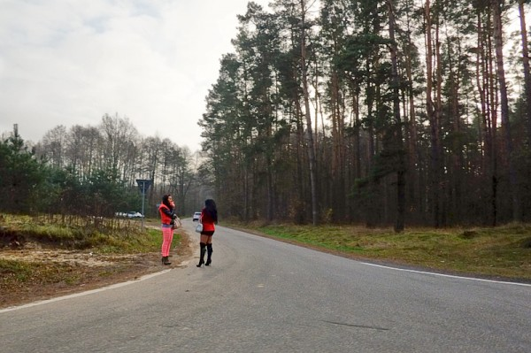 Two sex workers talking on the side of the road