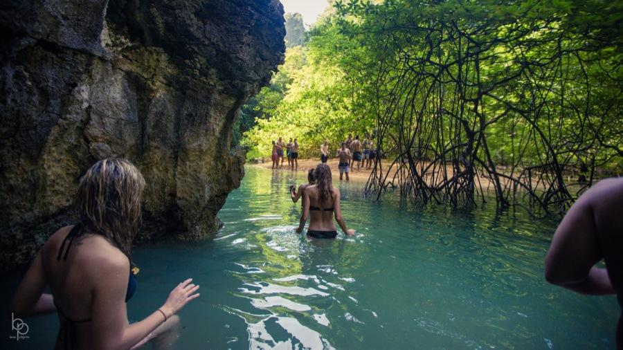 People walking through water near shore