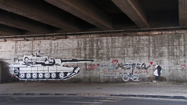 Tank vs. Biker is a mural by Ganzeer which clearly shows in black and white stenciling his opinion about the relationship between the army and the people. On the left, a huge tank rolls forward aiming at a young man riding his bike on the right. He carries the city on his head in place of a loaf of bread. The Arabic word for bread sounds similar to that for life.