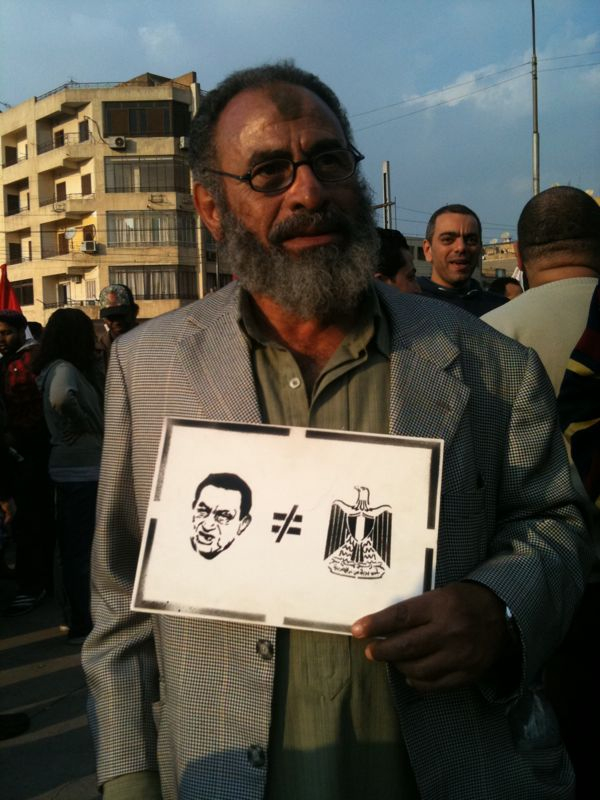 A citizen holds up one of Ganzeer's stencils which expresses that