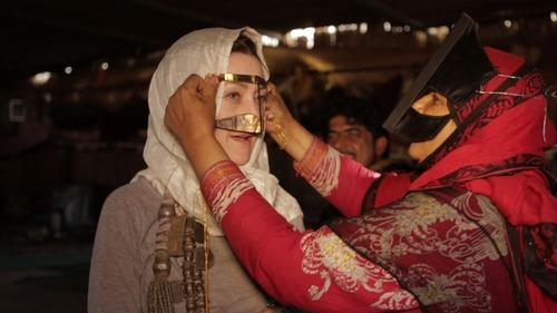 In Oman, they call the face mask a burqa. Sampta, a very traditional Bedouin woman, helps Froelich test it out. (Andrew Rothschild)