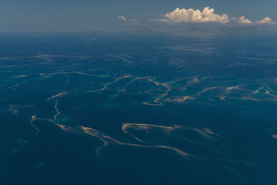 Aerial - of scattered small reefs with very possible coral spawn on the water's surface.