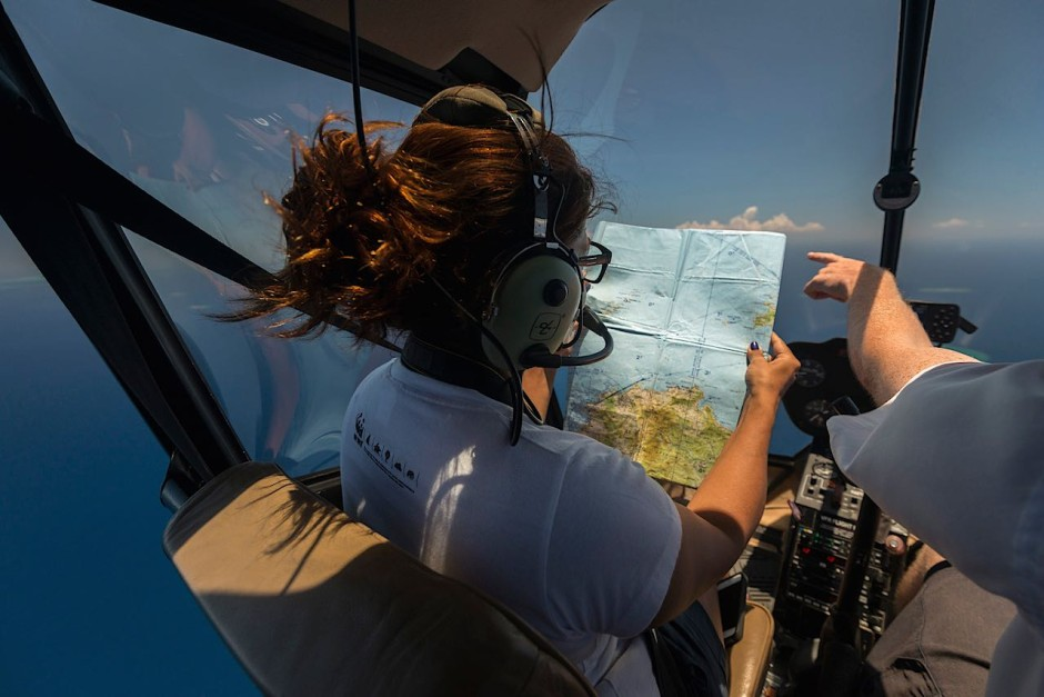 atricia Mallam of WWF South Pacific, aloft in a Robinson 44 helicopter, checks a map so she can locate the Yasawa reef, a popular spot for divers. Photo: Jürgen Freund