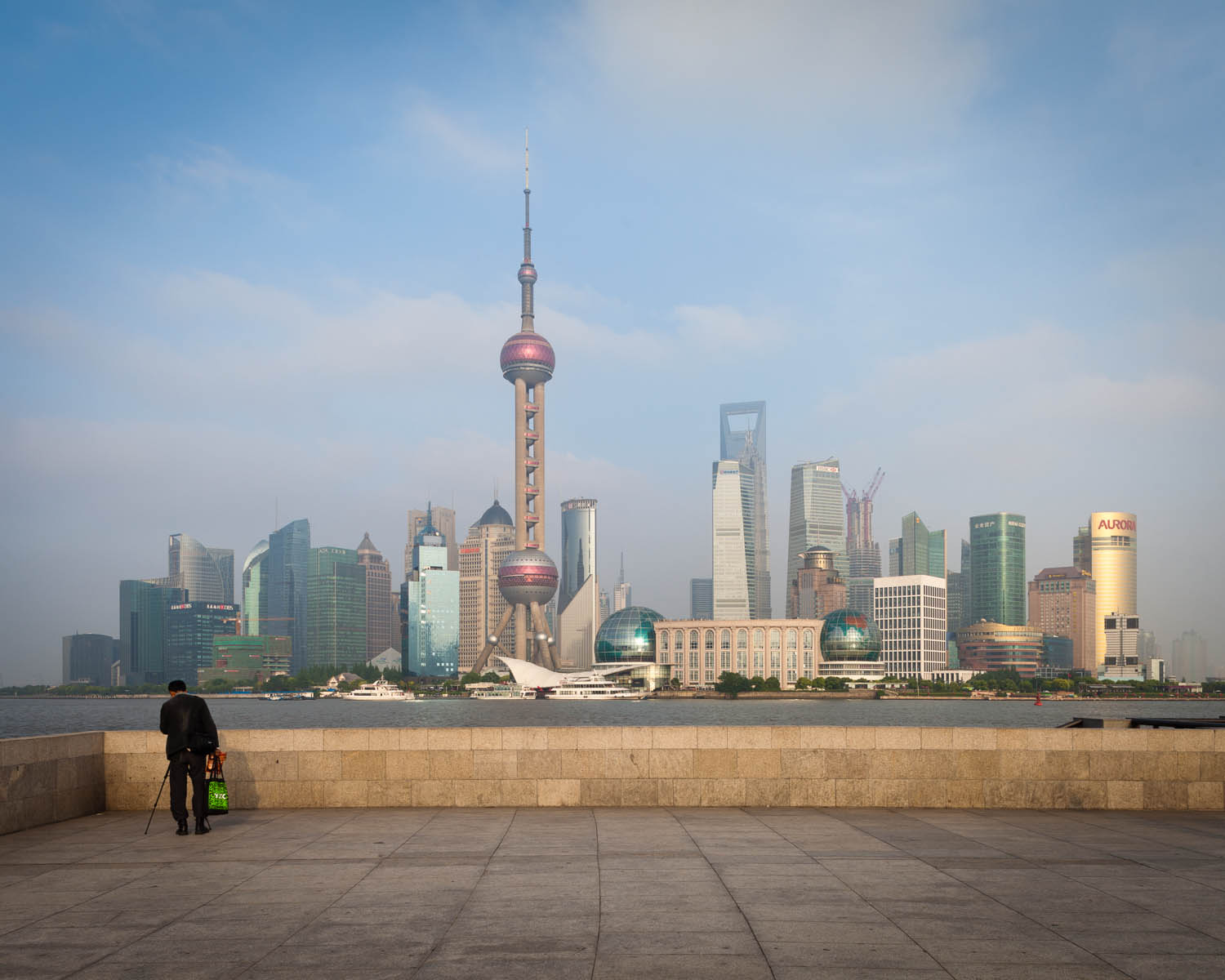 Photo: When I finally arrived at this stunning view oF Shanghai, I wanted to get a clear unobstructed view of thE skyline but there were so many people around. Instead, I chose to wait patiently until there weren't a group of people in the view. But then this photographer set up to take the same angle and it just felt like that was THE shot I was actually waiting for. I love how he shows the scale of the towering skyline.