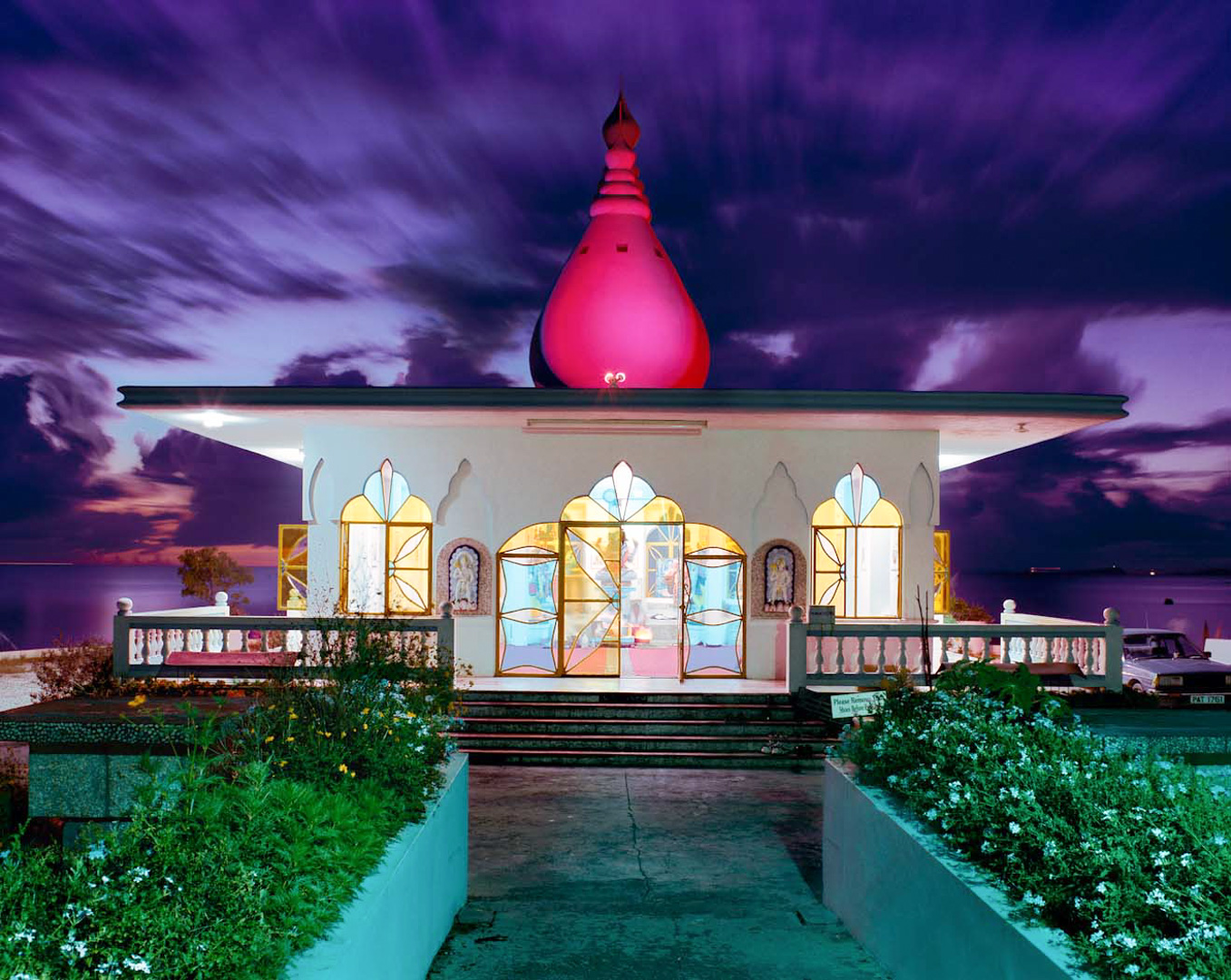 Photo: I made this photo with my Pentax 6x7 camera and a shift lens on a tripod using Kodak 160ASA film. Film is much less light sensitive than digital which means the dusk exposure took 15 minutes to expose at F11. During the long exposure the clouds were constantly moving directly behind the Hindu Temple. Combined with the multiple lights sources that cannot be recorded as neutral white light on one exposure, the results are a very colorful surreal photograph with great motion in the sky.