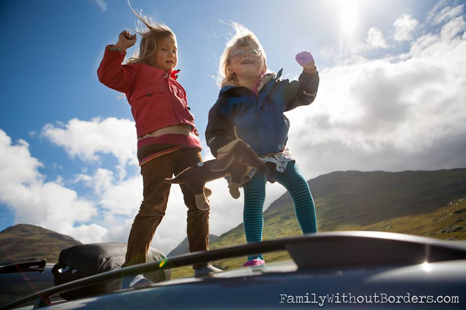 two little girls on top of car
