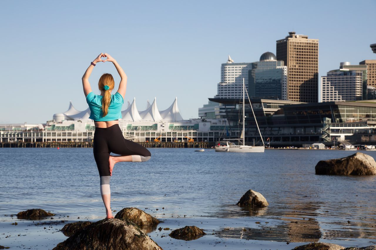 Woman practicing yoga in Stanley Park with Downtown City Skyline in the background. Taken in Vancouver, British Columbia, Canada.