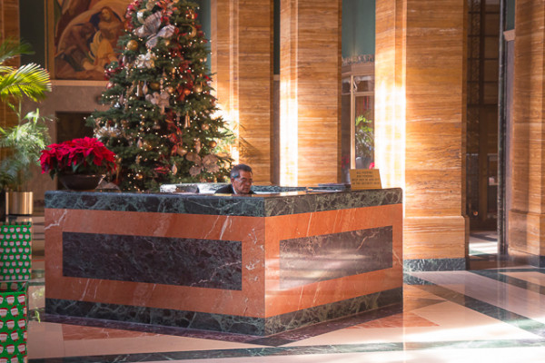 For the past fifty years, Los Angeles has seen a number of important office buildings lie empty, despite their grandiose designs incorporating complex marble and wood work. Not only are these buildings now seeing an increase in use, but rent is actually skyrocketing. Here, a receptionist works in the lobby of the Southern California Edison Power Company building, now owned by PacMutual. The building is currently being renovated to bring out it's 1930s charm.
