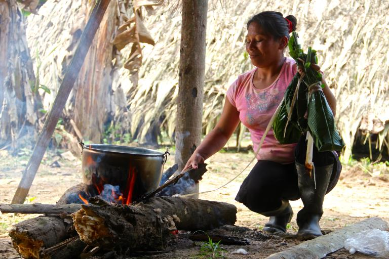 "Photo: Kawo, the other daughter of the family, wears Western clothes because she is regularly in contact with tourists in the Amazonia rainforest. She is cooking a traditional fish wrapped in a bijao leave (called ""maito de pescado"" in Spanish), a typical dish of the Amazon region.  Kamilia Lahrichi/GlobalPost"