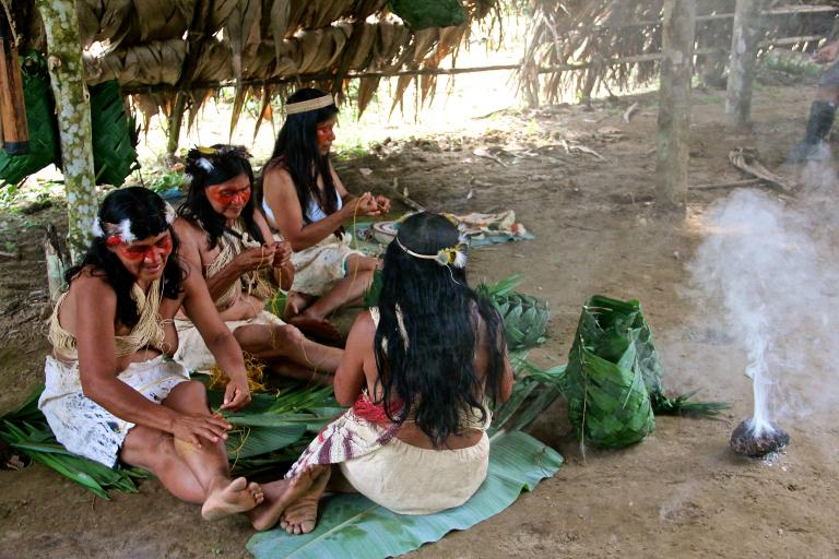 Photo: Kyenyé and the other women of the Daya family make traditional bags with banana leaves. The women manage to survive by selling crafts, mainly bracelets and wooden table mats, to eco-tourists. They sit next to smoke to ward off mosquitoes.  Kamilia Lahrichi/GlobalPost