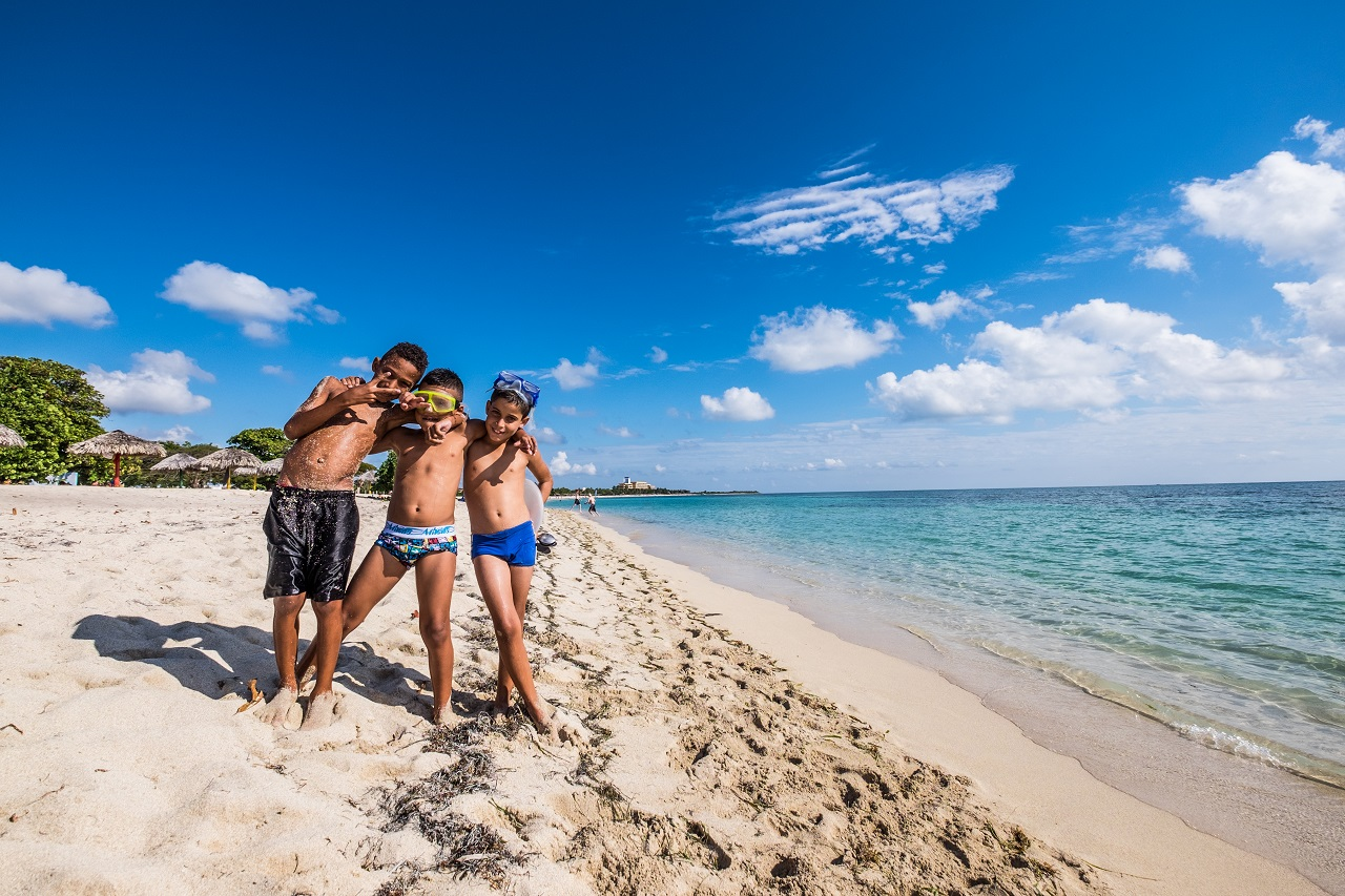 Cuba is home to some of the most beautiful beaches in the world. Three young boys enjoying the blue Caribbean. Photo: Jason Napolitano