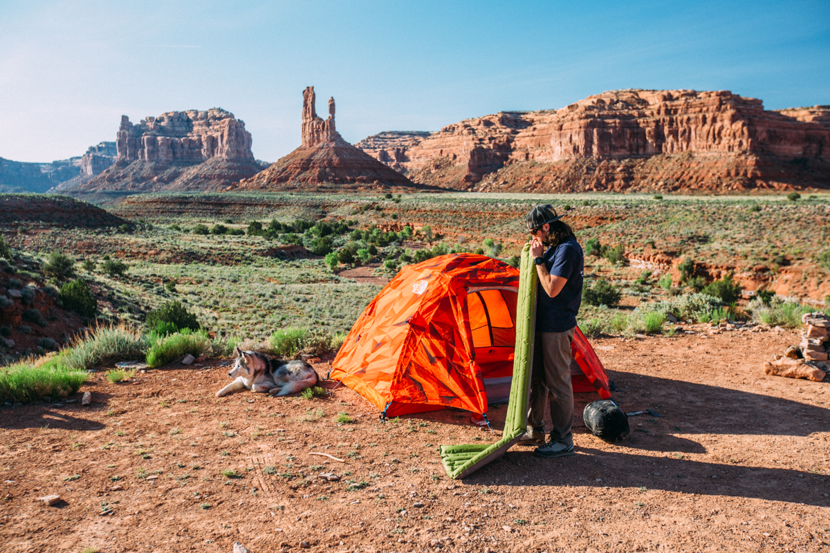 Kelly Lund setting up in monument valley. The sage scrublands along these valley floors make for some of the most aromatic camping experiences you'll ever have. Image by Scott Sporleder.