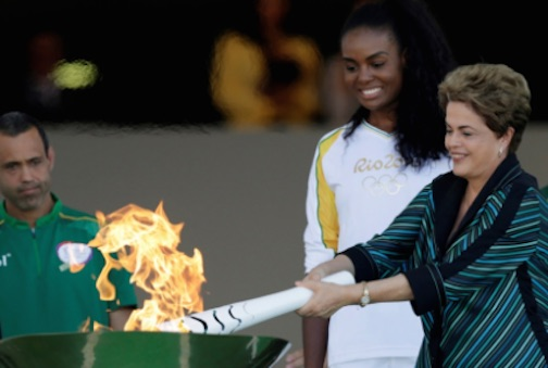 Photo: Brazil's President Dilma Rousseff lights a cauldron with the Olympic Flame next to Fabiana Claudino, captain of the Brazilian volleyball team, during the torch relay at Planalto Palace in Brasilia, Brazil, on May 3.  GlobalPost / Ueslei Marcelino/Reuters