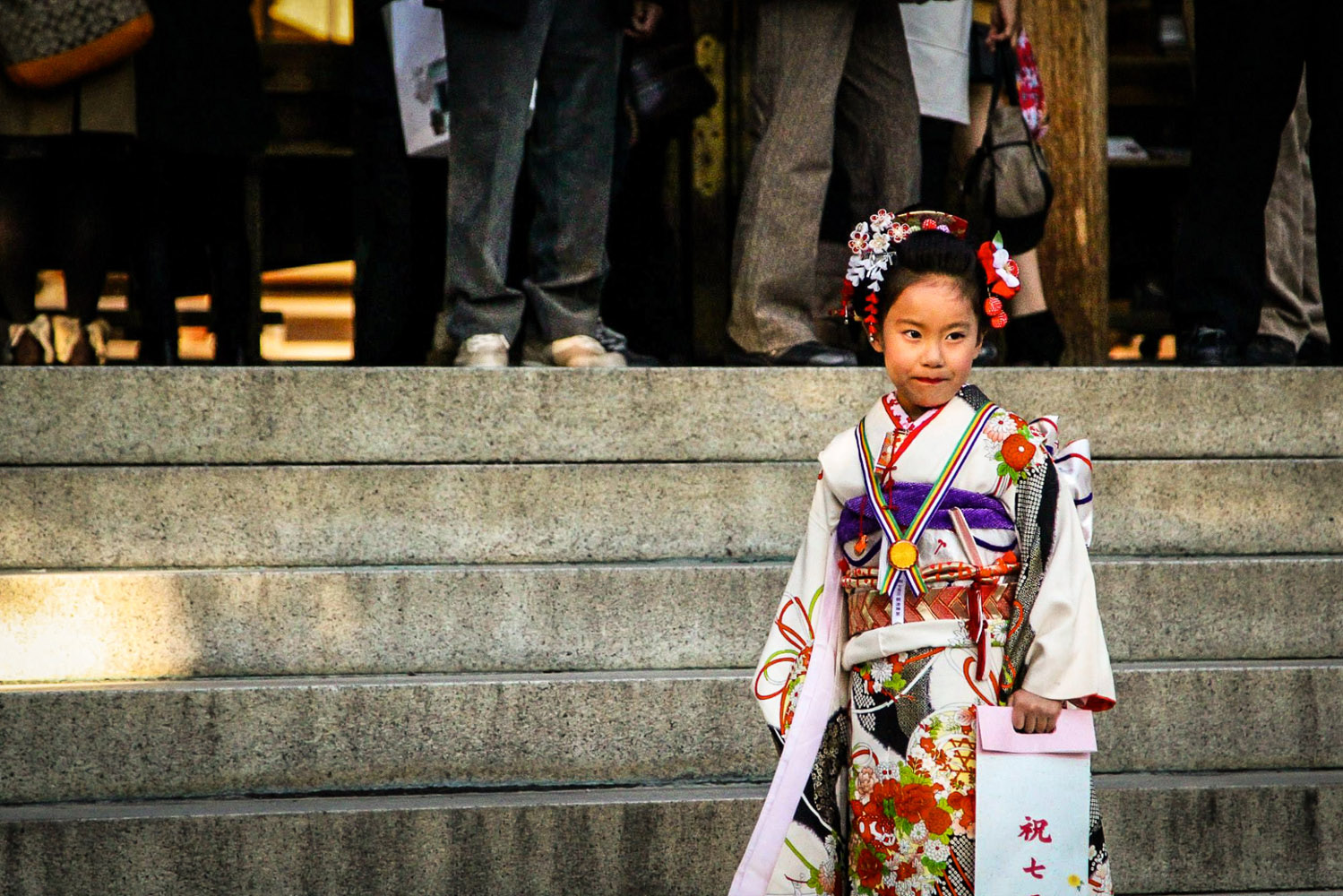 Young girl in a kimono stands on the main steps of a Shinto shrine, Tokyo