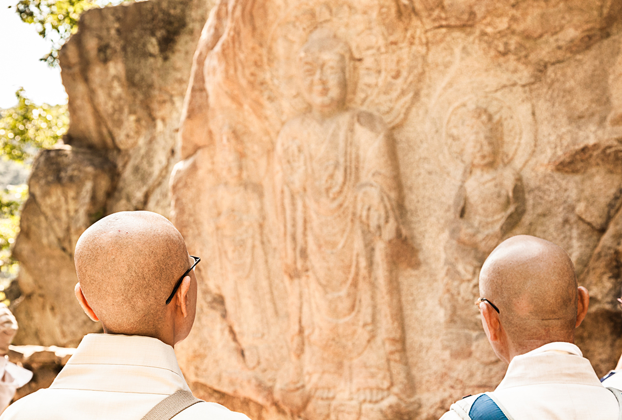 Faithful pilgrims stand before the famous – in Korea at least – rock carved Buddha triad – Yonghyeon-ri, Seosan