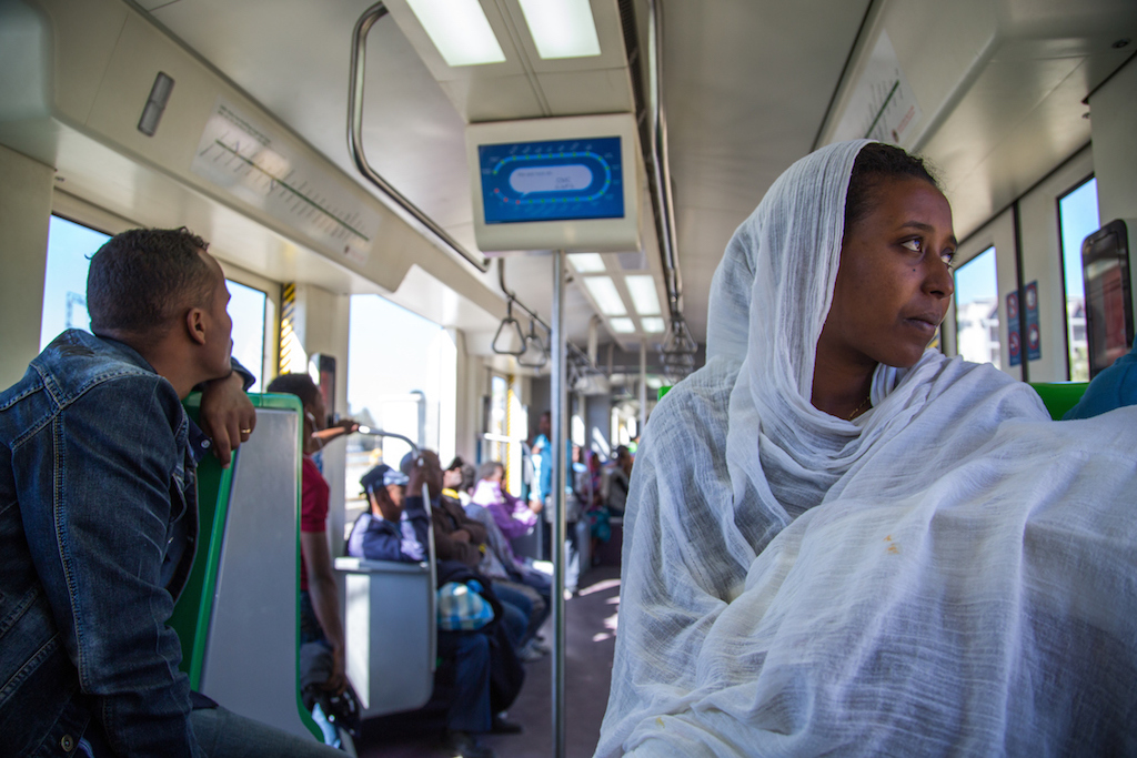 A lady holding her baby wrapped in a white shawl is transported on an Addis Ababa LRT. (Mulugeta Ayene/AP Images for C40)