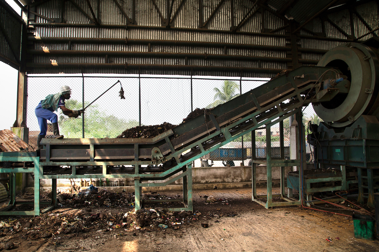 At the compost plant maintained of the KMDA Solid Waste Management Project, a worker uses the compost making machine. (Subrata Biswas/AP Images for C40)