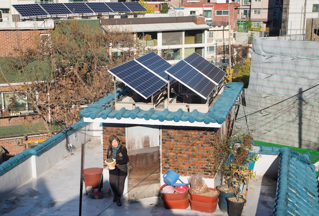 Won Young-Ae, 69, a resident at Sangol village carries a flowerpot on the roof of a house where cool roof and photovoltaic panels are installed for energy-efficient refurbishment by the city of Seoul's Energy Welfare Programme. Wednesday, Nov. 9, 2016. (Lee Jae-Won/AP Images for C40)