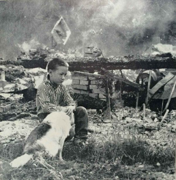 Sons of Freedom boy sits near the ashes of his burned home, 1962. Photo by George Diack