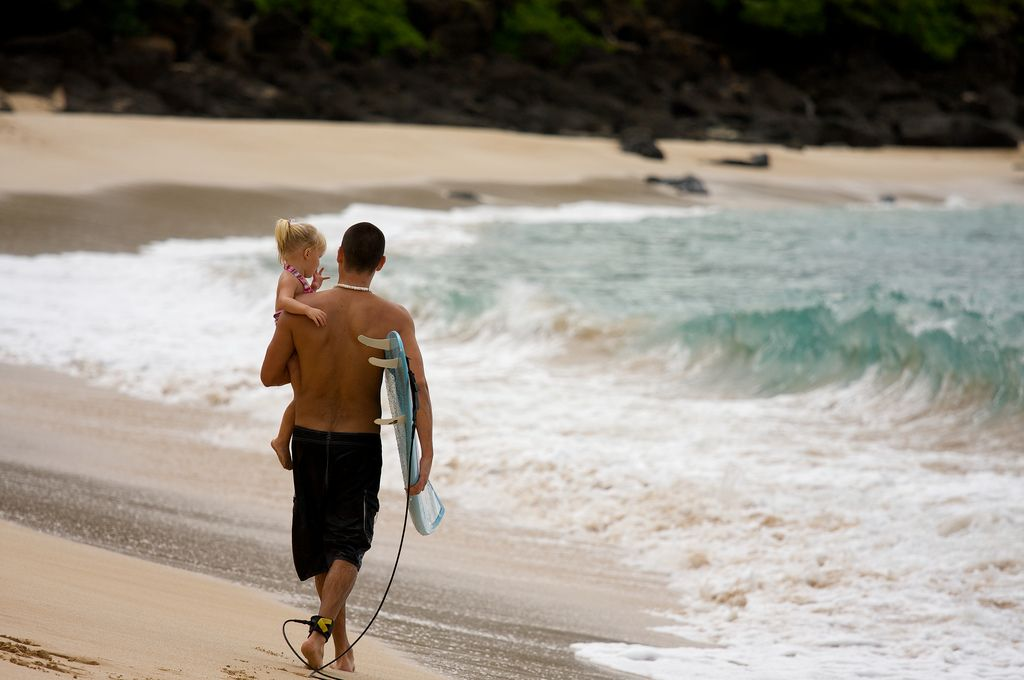 Kid and parent surfing Hawaii