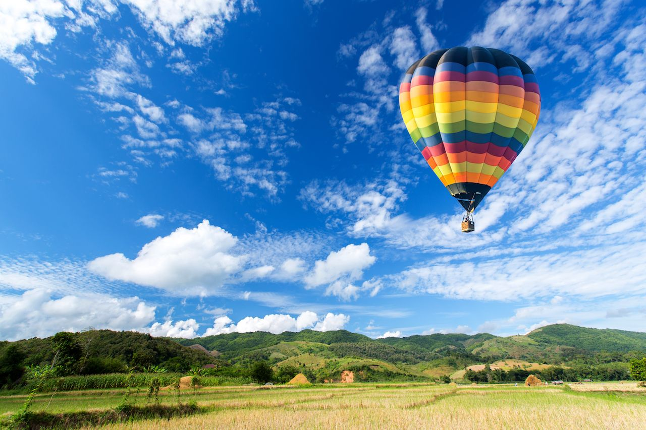 Propose in a Hot air balloon over the field with blue sky