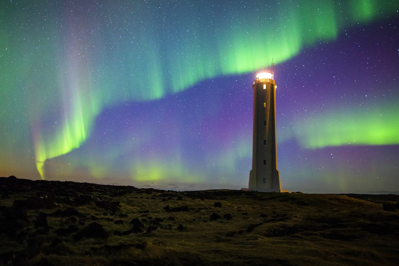 Aurora borealis on Iceland with lighthouse, road one