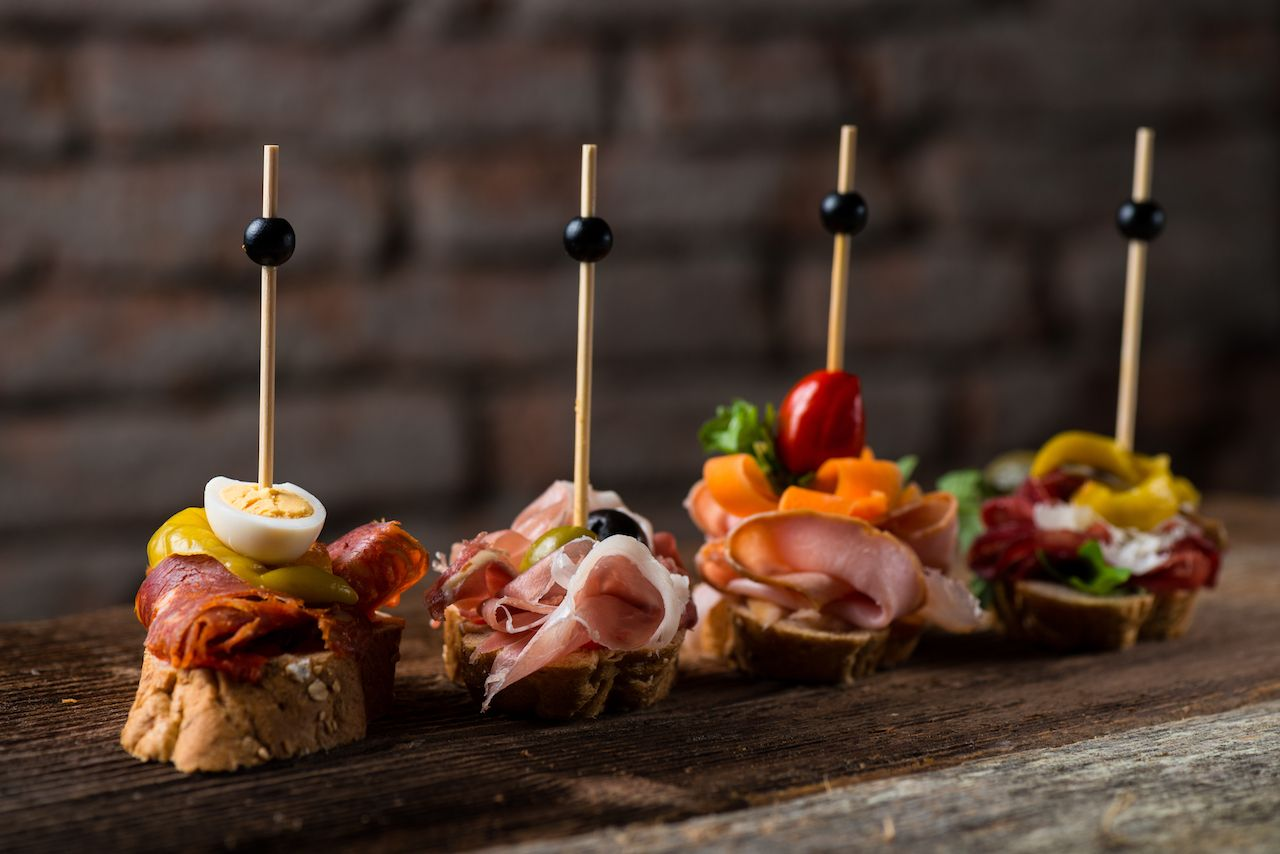 A selection of Spanish tapas served on a sliced baguette