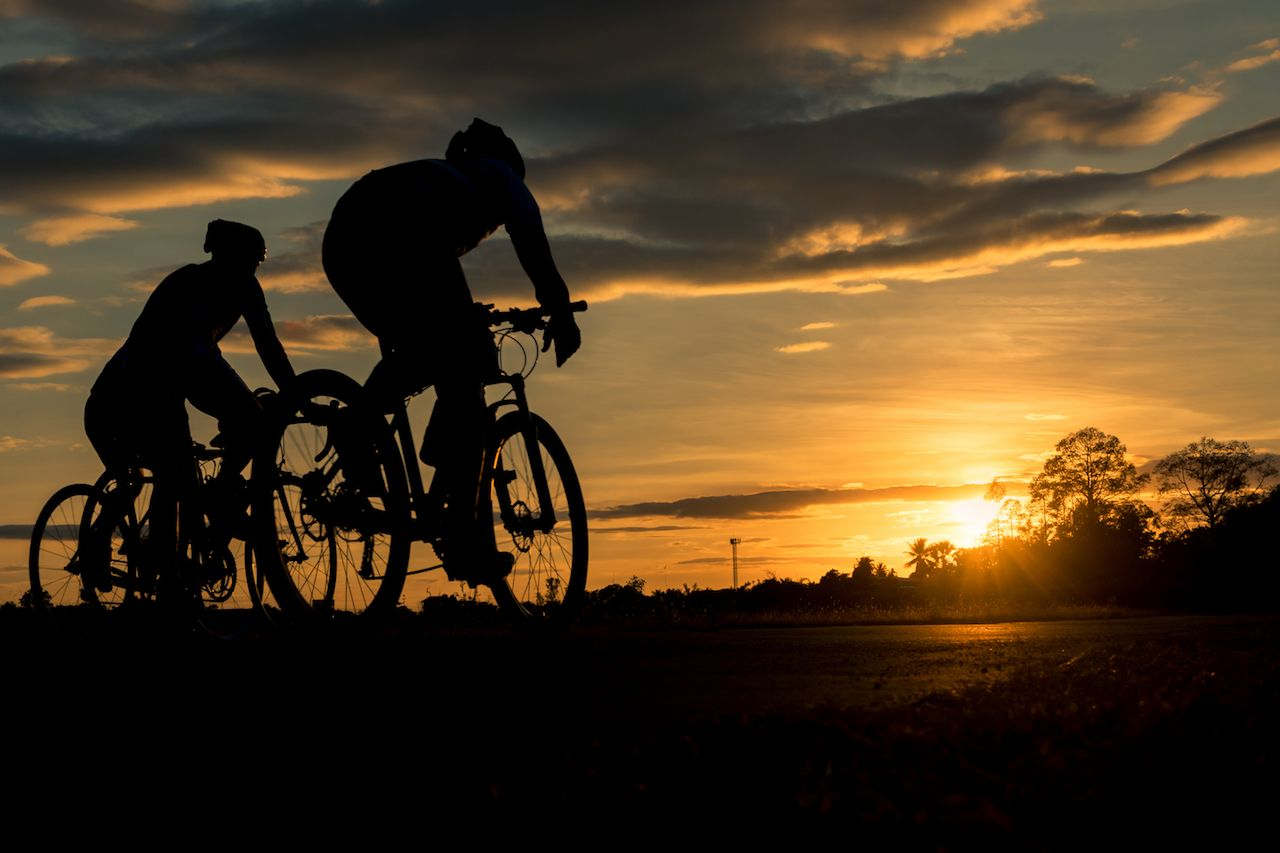 Men ride bikes at night with orange sky