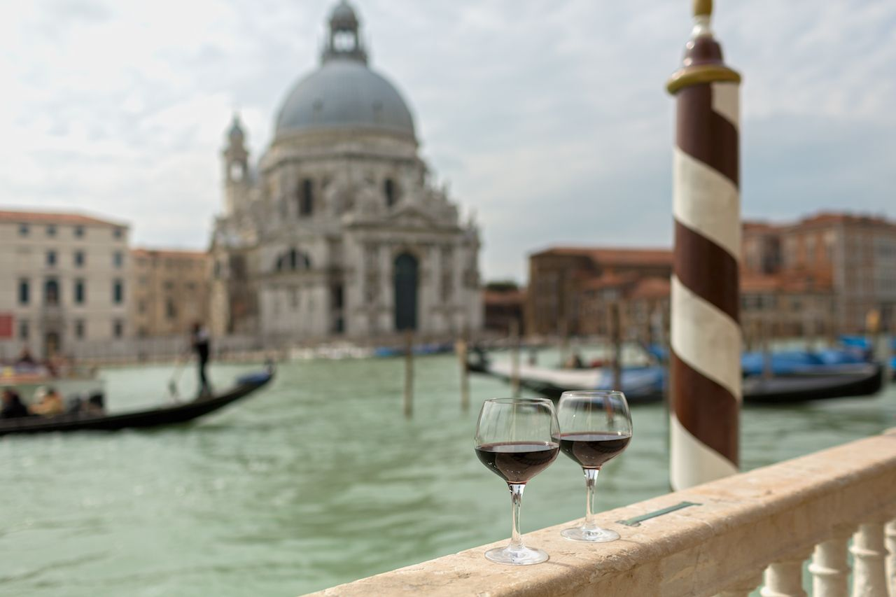 Two glasses of red wine on a railing in Venice