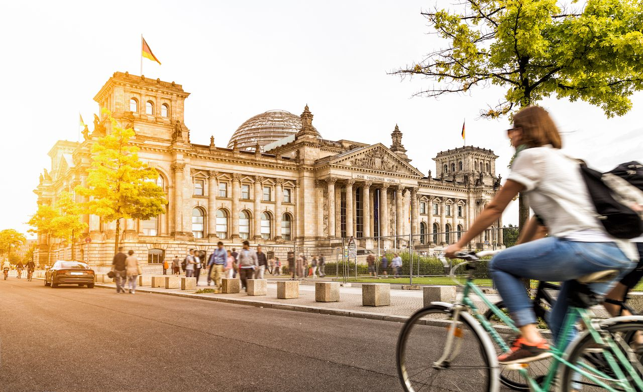 Woman riding bike by Reichstag in Berlin