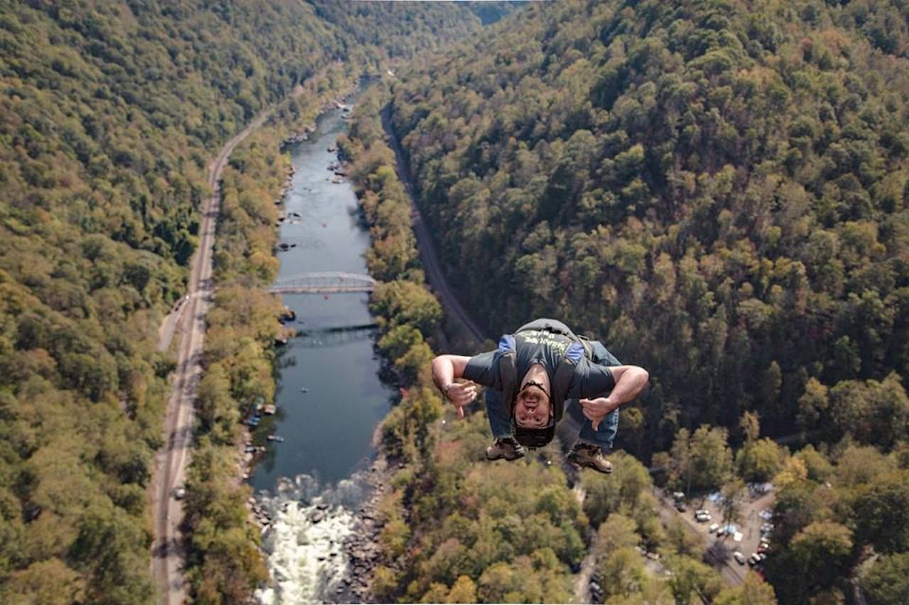Aerial view of base jumper suspended over river on Bridge Day