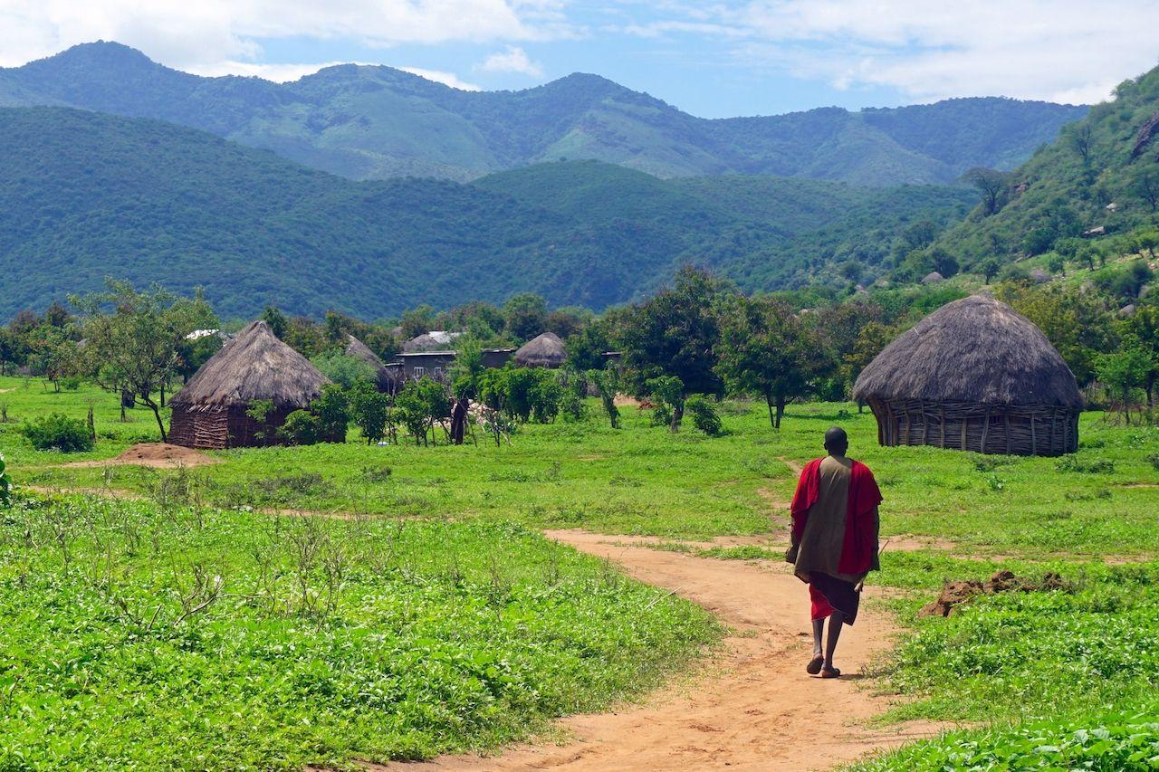 Masai man and village