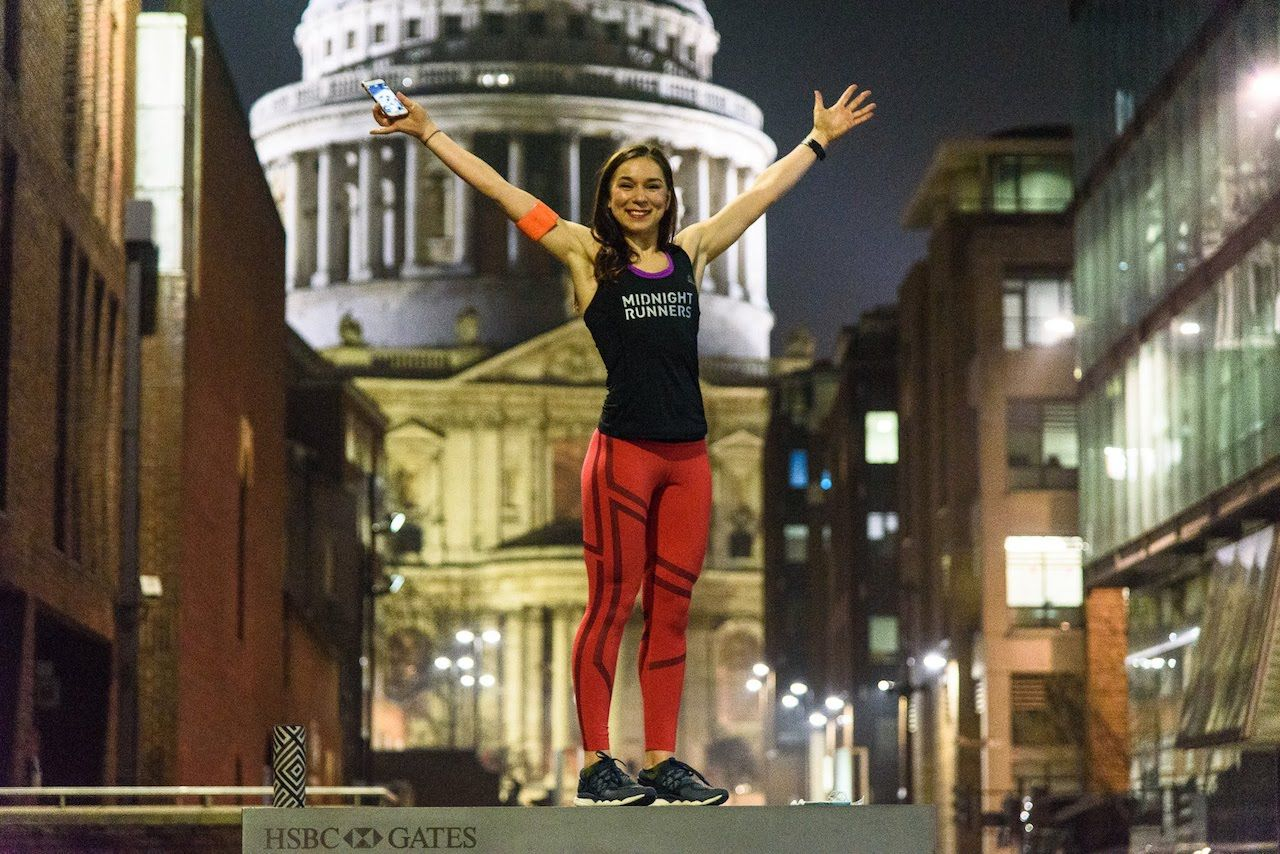 Midnight runner standing on podium with arms outstretched