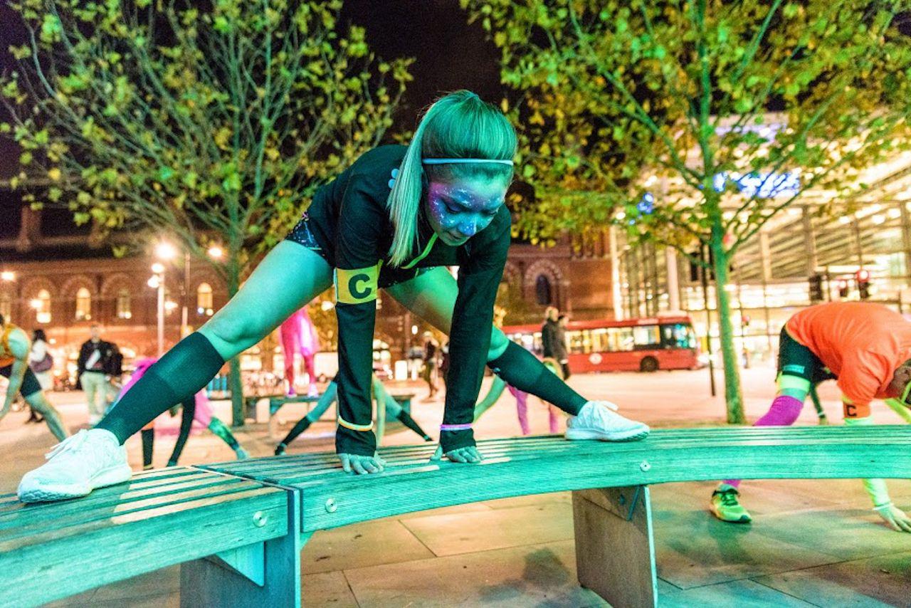 female urban night running stretching