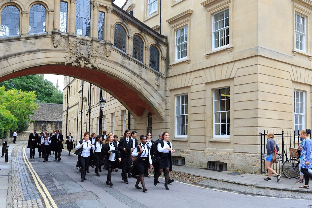 Graduates of Oxford University walk by Hertford College
