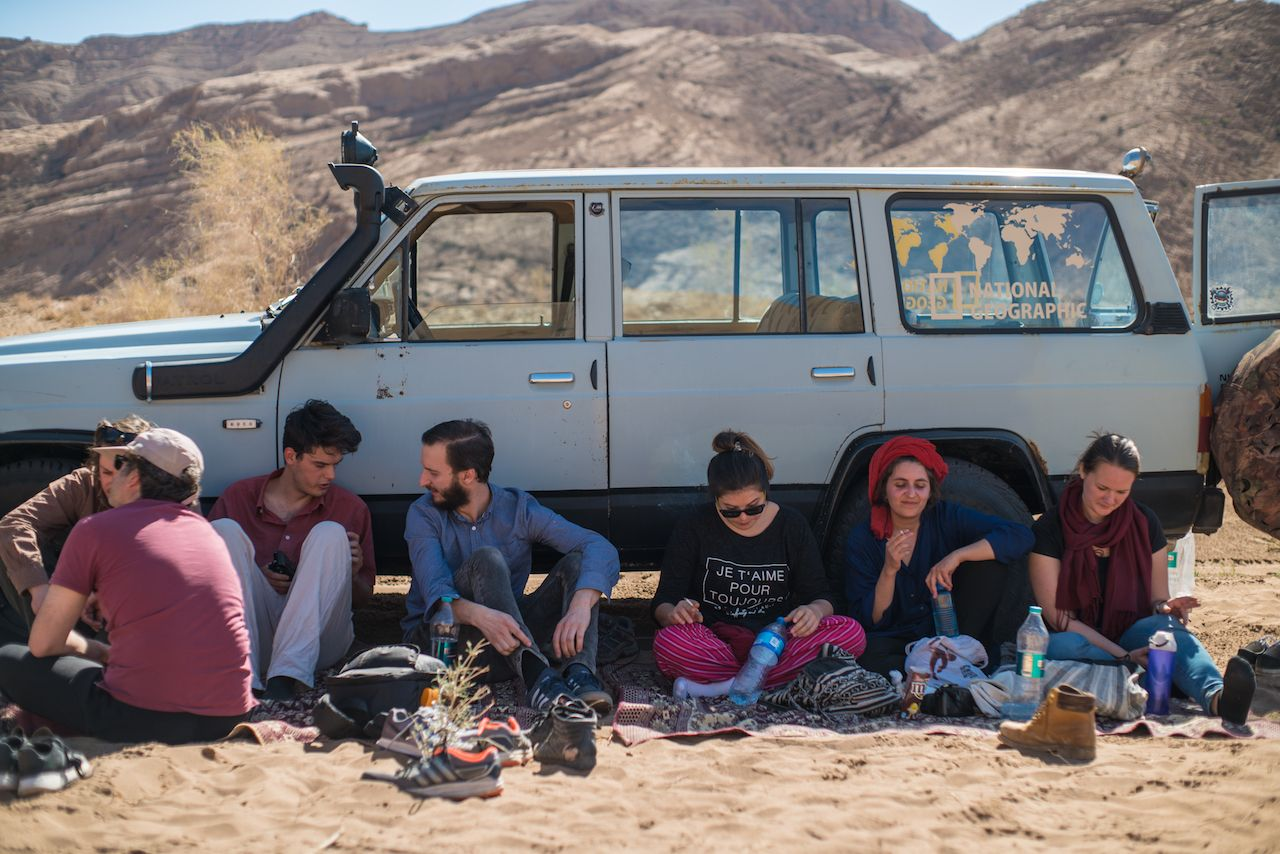 Sitting in front of a car in the Iranian desert