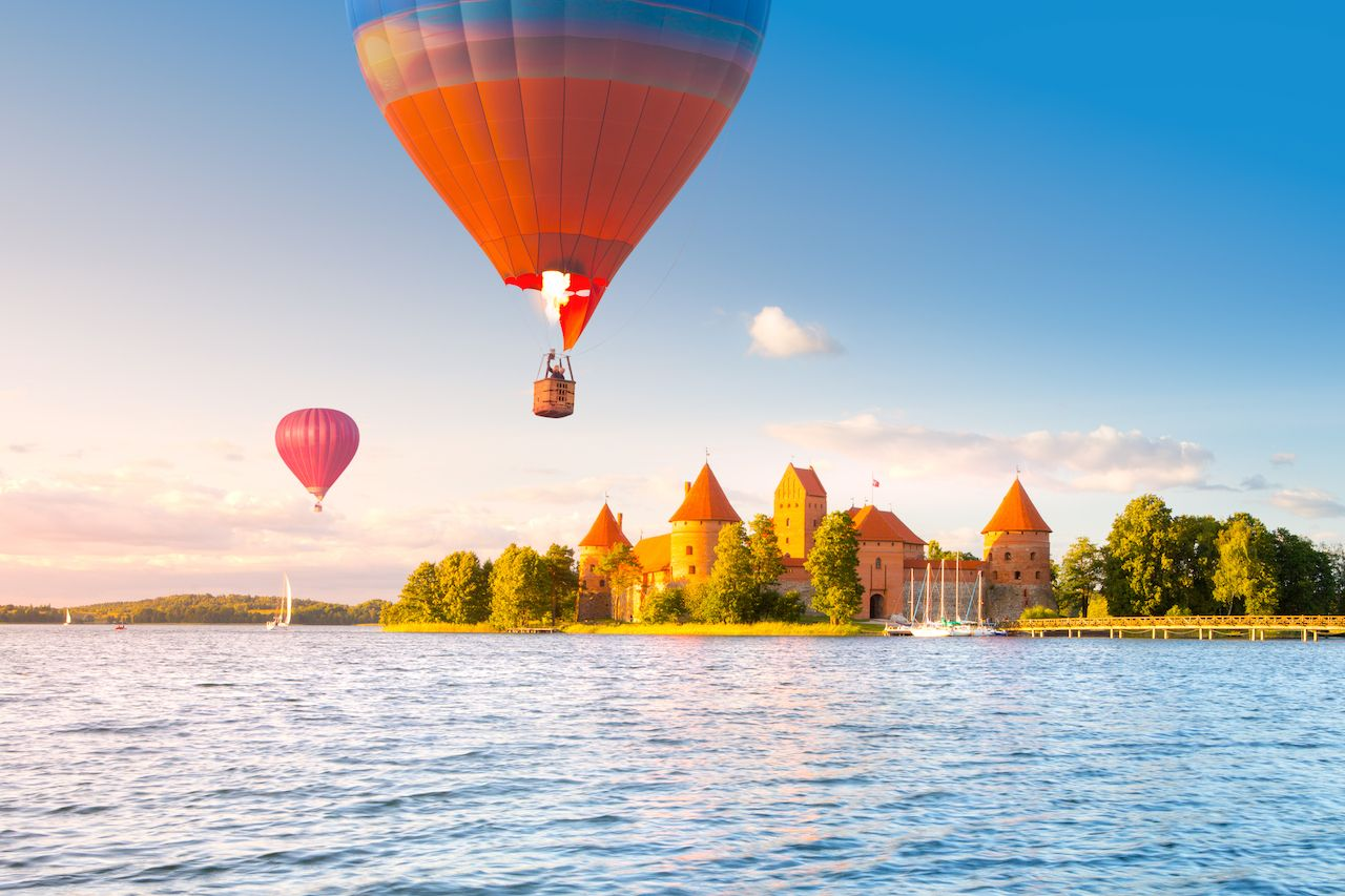 Landscape with red brick castle on island and flying air balloon in Trakai