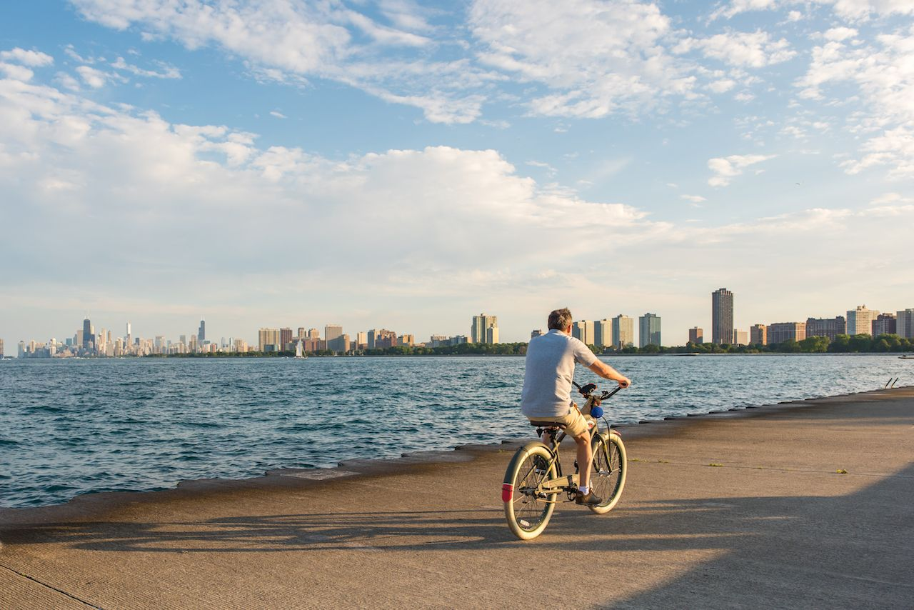 Man rides a bicycle along the lakeside path at Montrose Harbor in Chicago