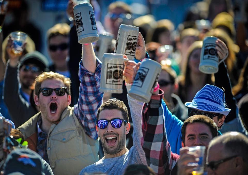 Men holding up beer mugs at Oktoberfest in Denver, Colorado