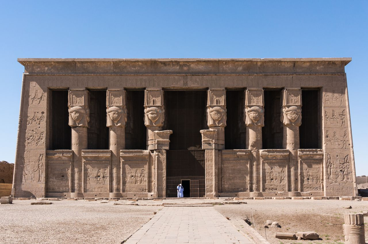 The Hathor temple with a two small figure of man in a white clothes. The Dendera complex near the Luxor in Egypt.